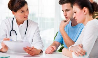 doctor speaking to couple about long term care plan for parents