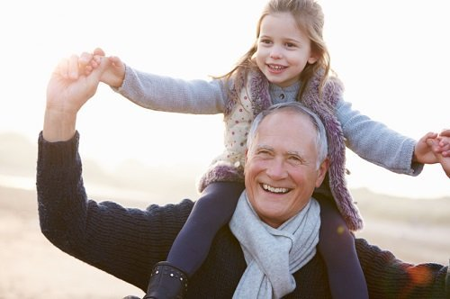 granddaughter on grandfather's shoulders on beach